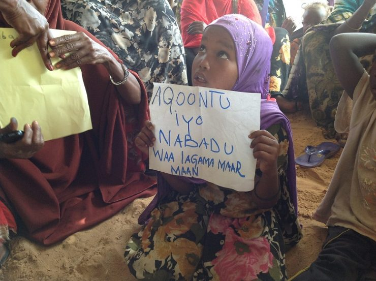 """Young IDP girl holding paper written with """"Its necessary to have peace and education"""""""